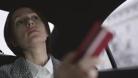 A mulher com cabelo marrom na equitação branca da blusa e do revestimento da verificação no carro e quer pagar com por um cartão vídeos de arquivo