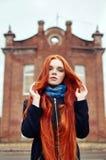 A mulher com cabelo vermelho longo anda no outono na rua Olhar sonhador misterioso e a imagem da menina Passeio da mulher do ruiv imagem de stock royalty free