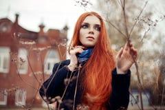 A mulher com cabelo vermelho longo anda no outono na rua Olhar sonhador misterioso e a imagem da menina Passeio da mulher do ruiv Fotos de Stock Royalty Free