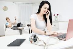 A mulher com cabelos pretos longos comunica-se através do telefone celular - o homem louro no fundo chama demasiado imagens de stock royalty free