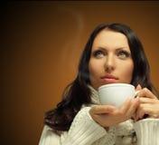 Mulher com café quente no fundo marrom Foto de Stock