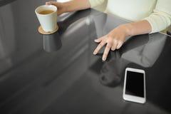 Mulher com caf? usando o painel interativo preto fotografia de stock