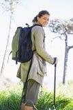 Mulher com caminhada de varas imagem de stock