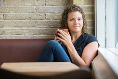 Mulher com a caneca de café que senta-se no bar Fotografia de Stock
