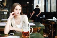 Mulher com a caneca de cerveja do álcool no café Imagem de Stock Royalty Free