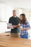 Mulher com carpinteiro Looking At Plans para a cozinha nova imagem de stock royalty free