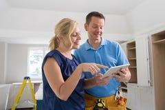 Mulher com carpinteiro Looking At Plans para a cozinha nova em digital foto de stock royalty free