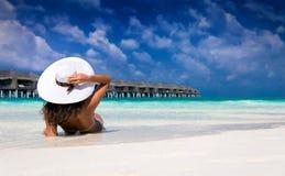 Mulher com chapéu branco que aprecia a praia imagem de stock royalty free