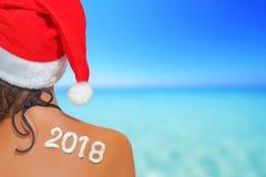 Mulher com chapéu de Santa e 2018 escrito nela para trás, no fundo azul do mar Fotografia de Stock