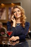 Mulher com cocktail que chama o smartphone na barra fotografia de stock