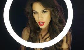 Mulher com composição desarrumado atrás do círculo fluorescente fotos de stock royalty free