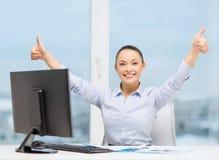 Mulher com computador, papéis que mostram os polegares acima Imagem de Stock