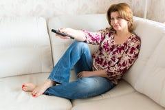 Mulher com controlo a distância da tevê que senta-se no sofá foto de stock