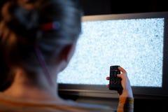Mulher com controlo a distância na frente do aparelho de televisão Fotos de Stock Royalty Free