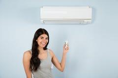 Mulher com controlo a distância na frente do condicionador de ar Fotografia de Stock Royalty Free