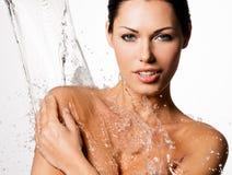 A mulher com corpo molhado e espirra da água Fotografia de Stock Royalty Free