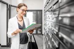 Mulher com correspondência perto das caixas postais imagens de stock