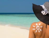 Mulher com creme sol-dado forma do sol Foto de Stock