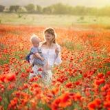 Mulher com a criança no campo com papoilas Fotos de Stock Royalty Free