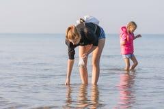 A mulher com a criança que anda ao longo da praia e recolhe conchas do mar Fotos de Stock Royalty Free
