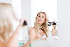 Mulher com denominação do ferro que faz seu cabelo no banheiro Fotografia de Stock Royalty Free
