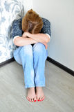 Mulher com a depressão que senta-se no canto da sala Fotos de Stock Royalty Free