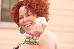 Mulher com dinheiro vermelho da terra arrendada do cabelo Curly Fotos de Stock Royalty Free