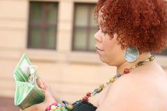 Mulher com dinheiro vermelho da terra arrendada do cabelo Curly Imagens de Stock