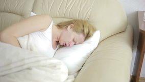 Mulher com a dor abdominal que encontra-se no sofá Analgésico bebendo dos comprimidos da menina filme