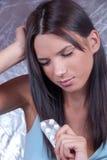 Mulher com a dor de cabeça que guarda tabuletas dos comprimidos Fotografia de Stock Royalty Free