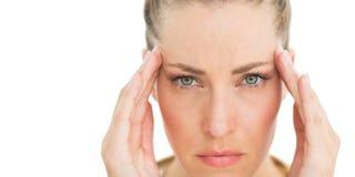 Mulher com a dor de cabeça que toca em seus templos que olha de sobrancelhas franzidas na câmera fotografia de stock royalty free