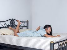Mulher com a dor lombar que encontra-se na cama Imagens de Stock