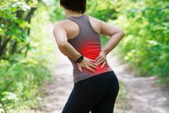 Mulher com dor nas costas, inflamação do rim, ferimento durante o exercício imagem de stock
