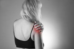 Mulher com dor no ombro Cause dor no corpo humano em um fundo cinzento Imagem de Stock