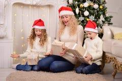 A mulher com duas crianças abre os presentes para o Natal do ano novo imagem de stock royalty free