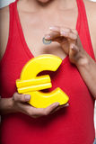 A mulher com economias pequenas e o euro deram forma a piggyban Imagens de Stock