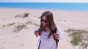 Mulher com escaladas da trouxa na duna de areia e olhares no mar da parte superior em férias vídeos de arquivo