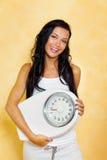 Mulher com escalas após uma dieta bem sucedida foto de stock royalty free