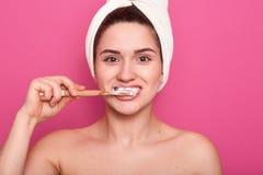 Mulher com escova de dentes, limpando seus dentes, levantando no banheiro com a cabeça desencapada e a toalha branca, procediment foto de stock