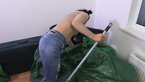 Mulher com a escova na sala desarrumado video estoque