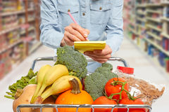 Mulher com escrita do carrinho de compras no bloco de notas Imagens de Stock