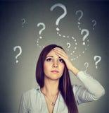 A mulher com a expressão preocupada da cara que olha acima tem muitas perguntas imagens de stock