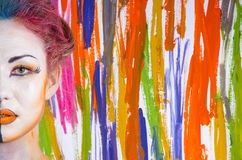 Mulher com face pintada em um fundo colorido Fotografia de Stock