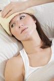 Mulher com febre na cama Imagens de Stock