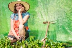 Mulher com a ferramenta de jardinagem que trabalha na estufa Fotografia de Stock