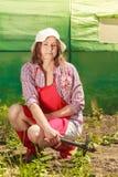 Mulher com a ferramenta de jardinagem que trabalha no jardim Fotografia de Stock Royalty Free