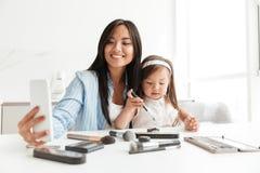 A mulher com filha pequena em casa faz dentro o selfie Fotografia de Stock