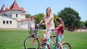 A mulher com filha pequena senta-se em bicicletas e fala-se filme
