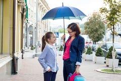 Mulher com a filha que anda junto à escola sob um guarda-chuva Fotografia de Stock Royalty Free