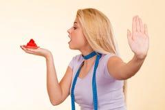 Mulher com a fita de medição que guarda a parada da exibição do queque Fotos de Stock Royalty Free